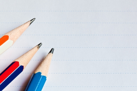 The background image of a piece of paper and pencils for writing