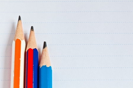 The background image of a piece of paper and pencils for writing photo