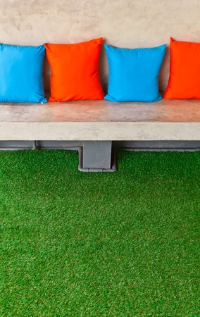 The closeup image of a concrete bench in the yard  with four colorful pillows