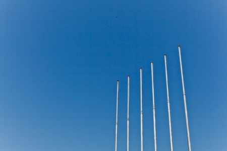 The empty metallic flagstaffs with the clear blue sky background Stock Photo