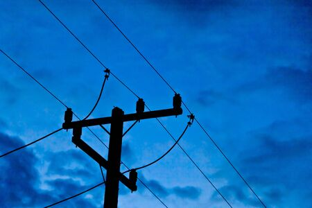 The silhouette image of an electricity post with blue sky
