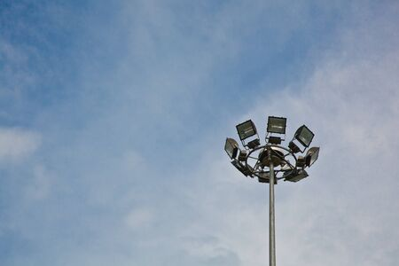 A metallic column structure of sport lights with the blue sky background