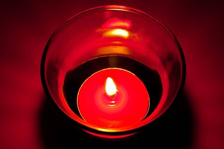 The closeup image of the burning red circular candle in the red glass photo