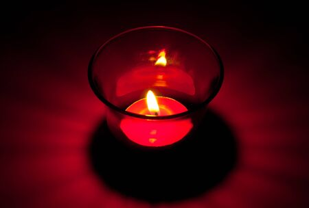 The closeup image of the burning red circular candle in the red glass