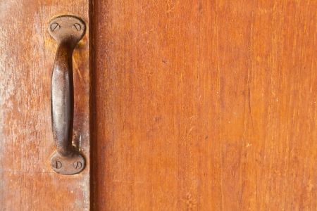 The old metallic handle attached on the wooden door Stock Photo