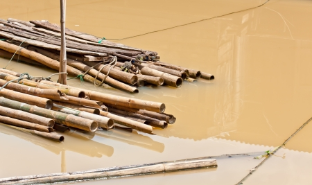 The closeup image of the floating binded bamboo in the canal