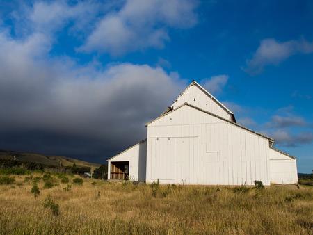 White Barn Under the Grey Clouds Фото со стока