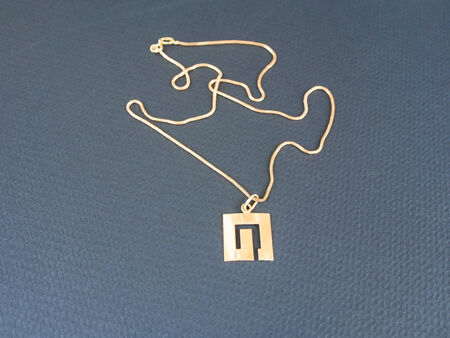 Pendant on golden chain isolated on the black