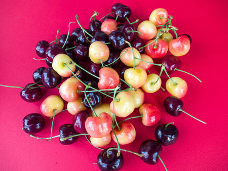 Cherries on the red background photo