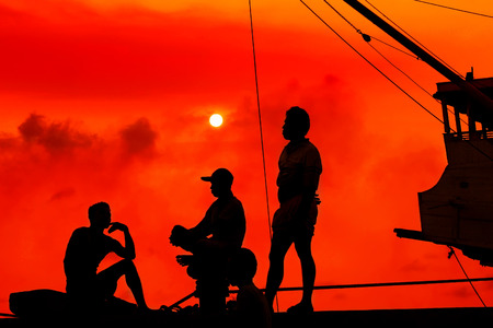 after hours: The silhouette of three Phinisi crews after working hours