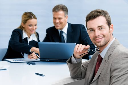Smiling satisfied businessman looking at camera with his colleagues in the background during a meeting in the office Stock Photo - 7889397