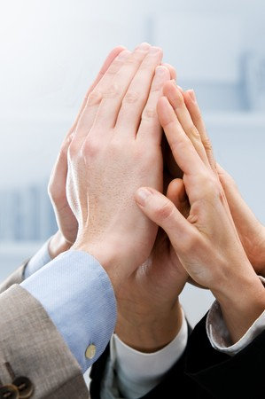 Group of hands raised up for an high five in the office. Symbol of teamwork, victory and success photo