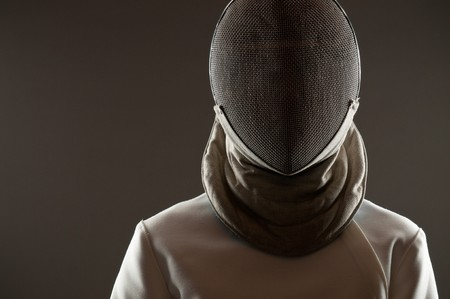 Studio portrait of fencing athlete wearing face protective mask, copy space