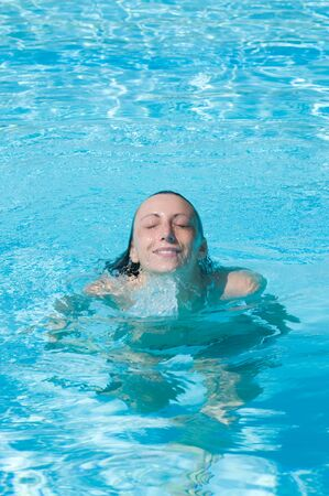 Beautiful young woman emerges after a dive in the swimming pool photo