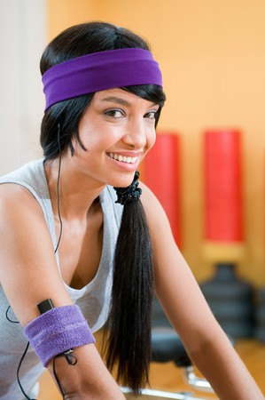 Smiling beautiful latin girl listening music during fitness exercising at gym photo