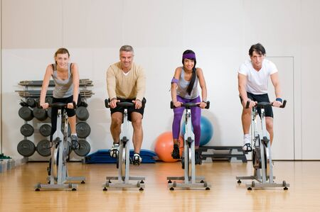 cycle ride: Happy active people exercising with bicycles in a gym. Front view