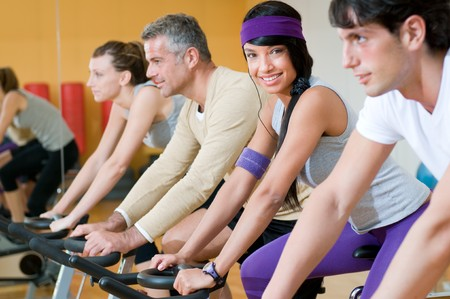 Latin girl smiling and looking at camera while exercising with spinning bicycles in group at gym photo