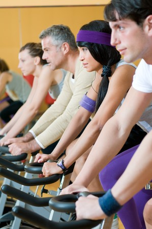 Group of healthy people doing spinning exercise at the gym photo