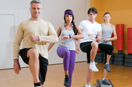 Group of healthy people with instructor doing aerobic exercises with step at gym