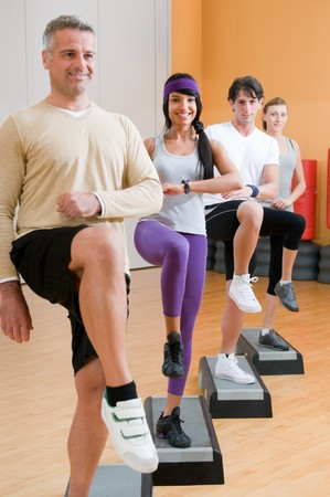 Group of healthy people with instructor doing aerobic exercises with step at gym Stock Photo - 7889460