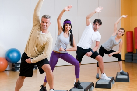 Healthy people doing aerobic exercises together at gym photo