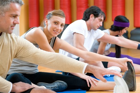Smiling girl looking at camera during stretching exercises with her class at gym photo