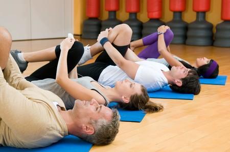 stretching: Clase de gente de fitness feliz en una fila haciendo algunos aer�bico estiramiento despu�s de entrenamiento en gimnasio  Foto de archivo