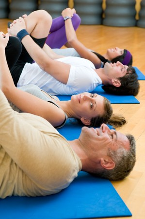 Happy fitness people in a row doing some aerobic stretching after workout at gym photo