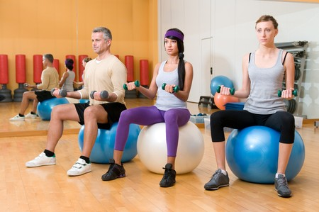 Healthy people lifting weights and sitting on a fitness ball at gym photo