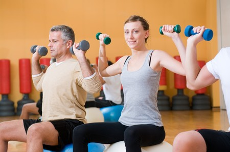 Young lady smiling and looking at camera while lifting weigths on a fitness ball at gym Stock Photo - 7889469