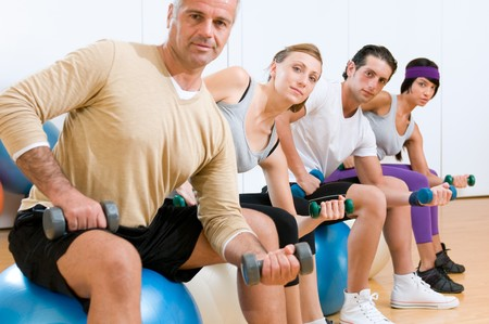 Young people with instructor lifting weights on a fitness ball at gym Stock Photo - 7889381