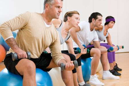 Healthy young people lifting dumbbell and sitting on a fitness ball at gym, instructor on foreground Stock Photo - 7889443