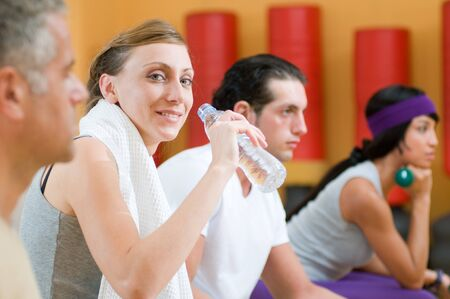 Beautiful young lady drinking bottle of water during a break at gym Stock Photo - 7889438