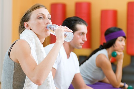 Beautiful young lady drinking bottle of water during a break at gym photo