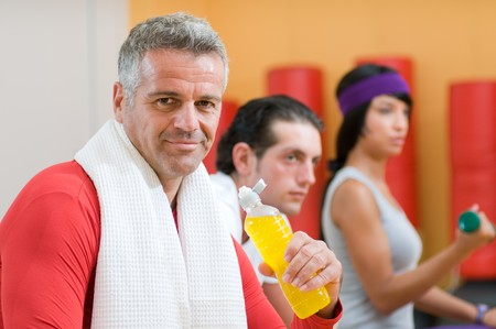 Mature man drinking energy drink during a break at gym photo