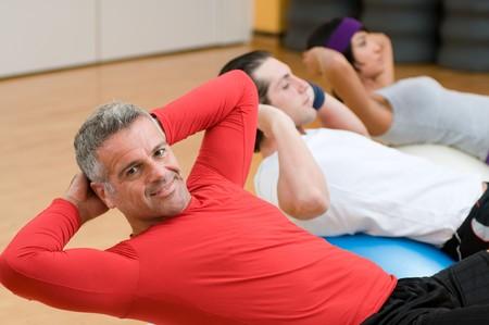 abdomen fitness: Personas saludables con instructor maduro haciendo abdominales en gimnasio  Foto de archivo