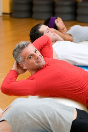 pilates man: Healthy people with mature instructor doing sit-ups on fitness ball at gym Stock Photo