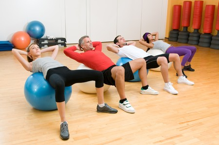 Fitness class making sit-ups on fitness ball at gym, mature instructor in the centre photo