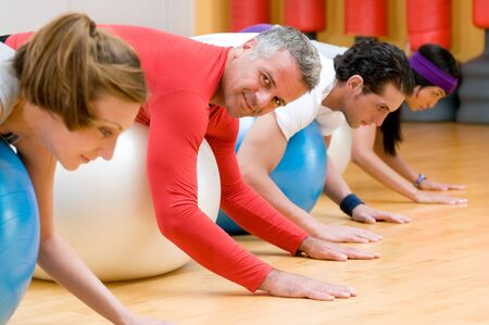 Fitness class lying on front on fitness balls at gym, mature instructor in the centre Stock Photo - 7889495