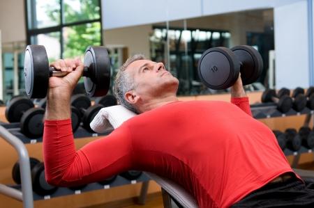 hombre flaco: Hombre maduro dumbells de elevaci�n a gimnasio fitness
