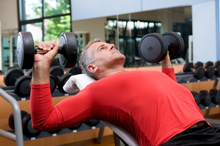 Mature man lifting dumbells at fitness gym photo