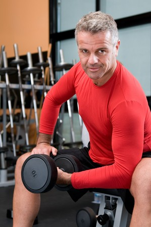 Happy satisfied mature man lifting weights at gym photo