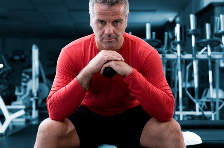 fitness instructor: Concentrated mature man looking at camera at gym Stock Photo