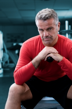 indoor sport: Mature personal trainer looking at camera with serious expression at gym
