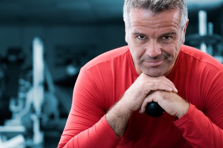 instructor: Mature personal trainer looking at camera with satisfaction in a gym Stock Photo
