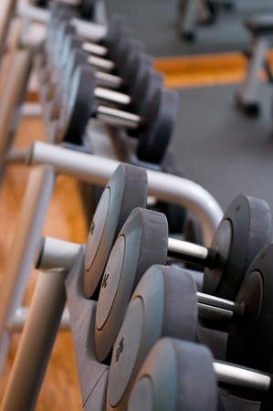 Serie of dumbbells in a row at gym, selective focus photo