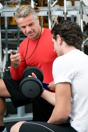 Mature instructor checking and supervising fitness training at gym photo