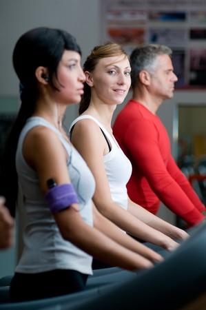 Young woman smiling at camera while walking on a treadmill at gym photo