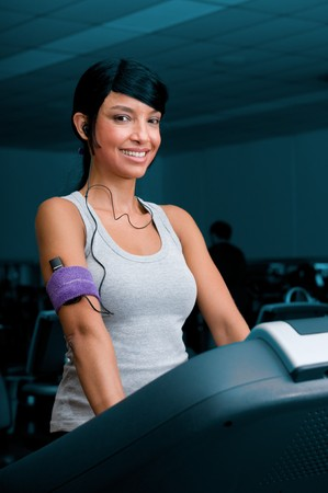 Beautiful young latin woman smiling and listening music while walking on a treadmill at gym photo