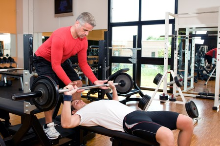 instructors: Young man doing weigths on a bench press with the help of the mature instructor at gym